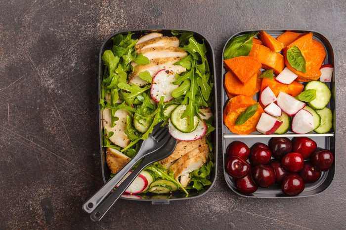 Healthy meal prep containers with grilled chicken with salad, sweet potato, berries, fruits and vegetables. Takeaway food.