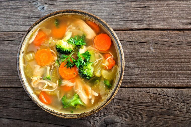 Homemade chicken vegetable soup, overhead, close up view on an old wood background