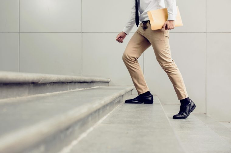 Businessman walking upstairs holding document, close up legs