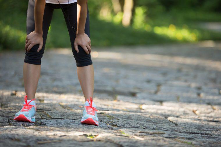 female runner hands on knees tired
