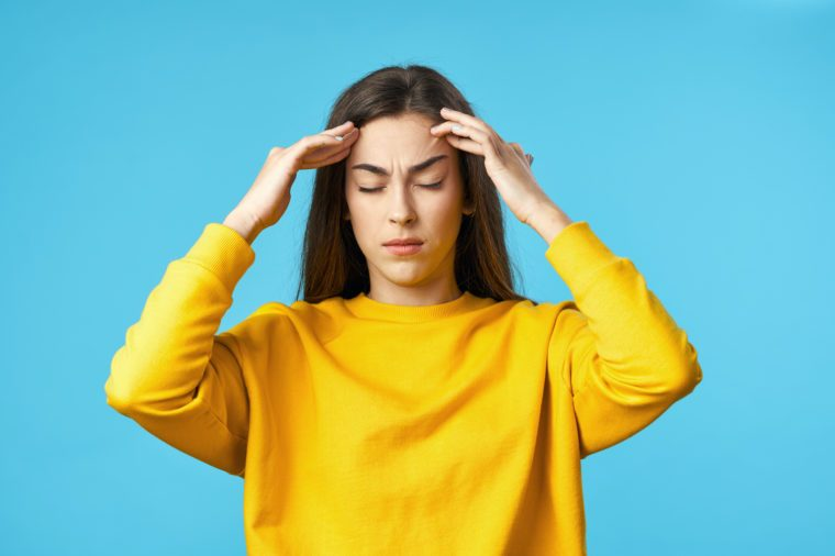 yellow sweater woman headache migraine blue background