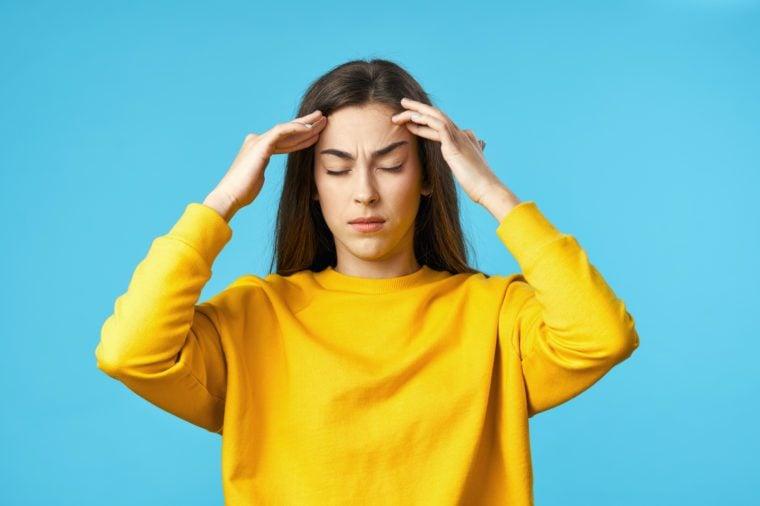 yellow sweater woman headache migraine blue background