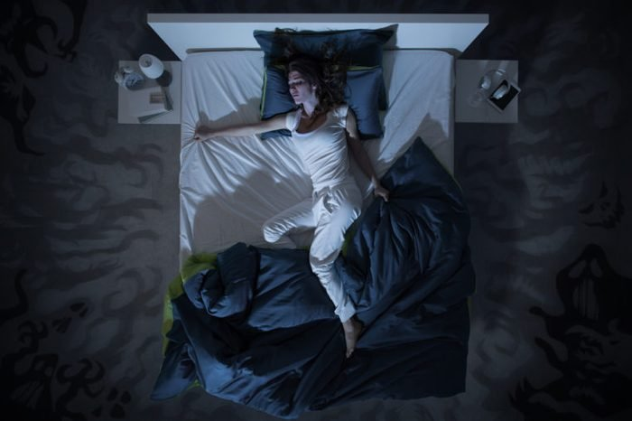 woman in bed at night trouble sleeping sweats