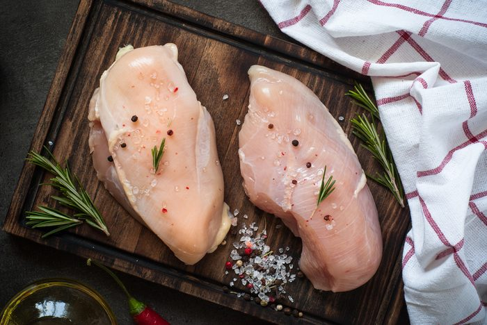 Raw chicken fillet on cutting board with sea salt pepper rosemary. Food background, cooking ingredients. Fresh meat.