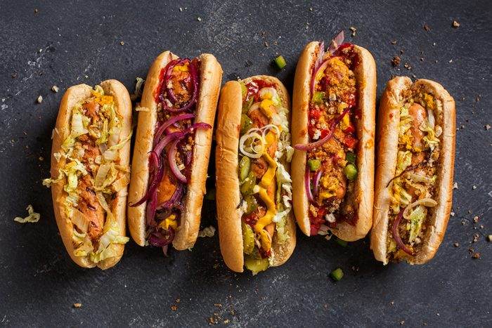 Hot dogs with a sausage on a fresh rolls garnished with mustard and ketchup and served with different toppings.