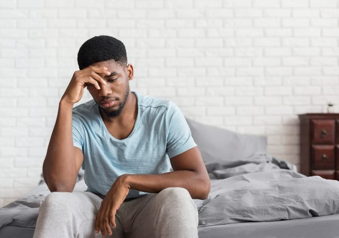 Bad mood in morning. Young depressed african-american man sitting on bed and consider about problems, copy space