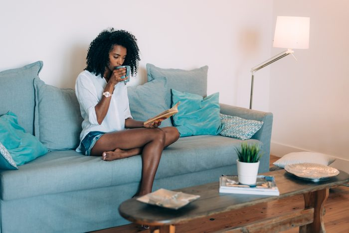 Beautiful young black woman seating in the sofa reading a book and drinking coffee