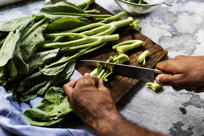 Closeup of hands with knife cutting chinese kale on cut board