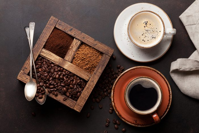 Coffee cup, roasted beans and ground coffee. Top view