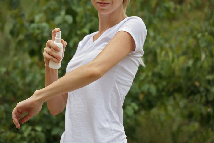 Mosquito repellent. Woman using insect repellent spray outdoors.