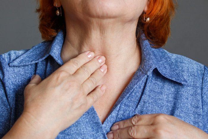 An elderly woman feels her thyroid gland.