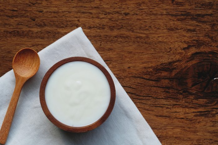 Plain organic yogurt in wooden bowl and wood spoon on wood texture background, copy space