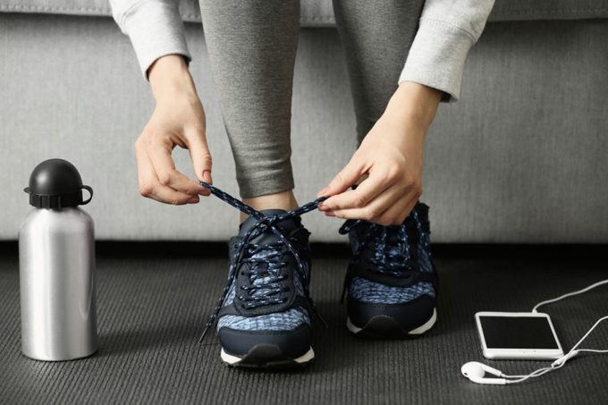 Woman tying up running shoe