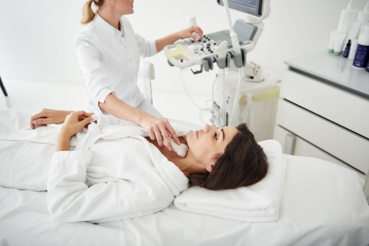 Side view portrait of attractive young woman in white bathrobe receiving ultrasound scanning of thyroid