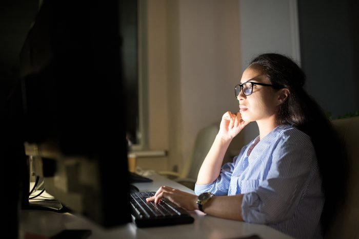 Side view portrait businesswoman working at computer late at night in dark office, copy space