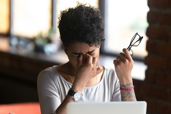 African American woman taking off glasses, feel eye strain, massaging nose bridge, tired female feeling discomfort after long wearing glasses at workplace, work with computer, bad eye vision close up