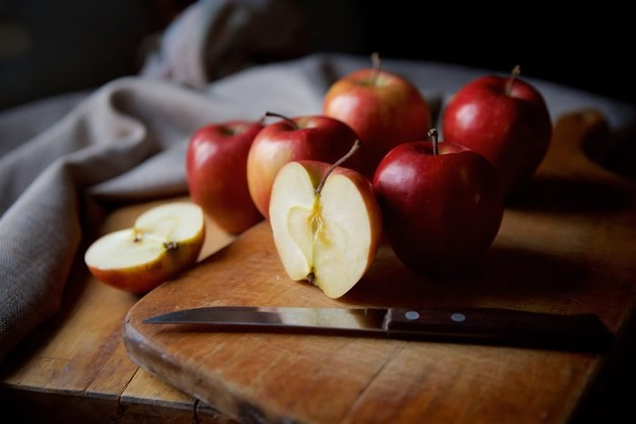 red apples and knife on wooden table