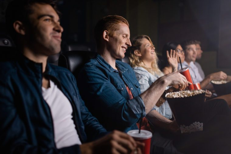 Young man with friends watching movie in cinema. Group of people in theater with popcorn and drinks.