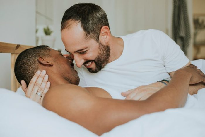 Gay couple making out in bed