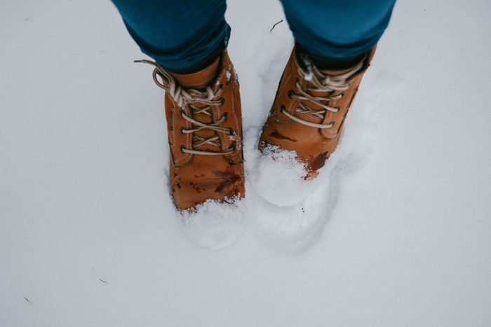 Vintage pair of yellow working and trekking boots, stepping on snow-covered surface.