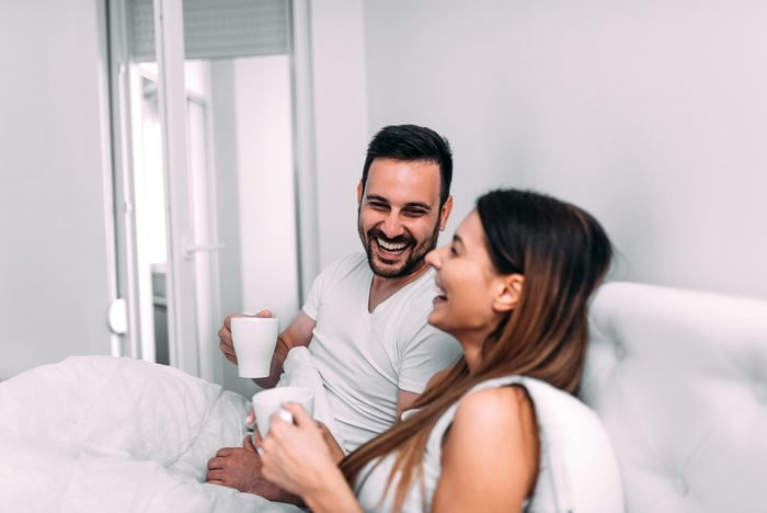 Couple in bed drinking coffee and laughing.
