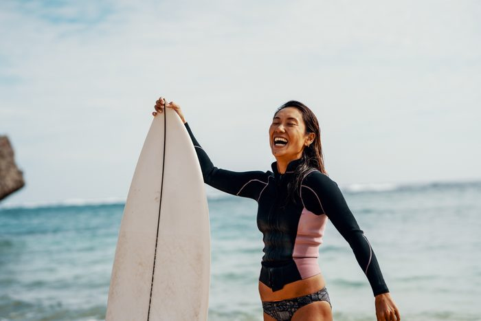 woman with surfboard on beach smiling