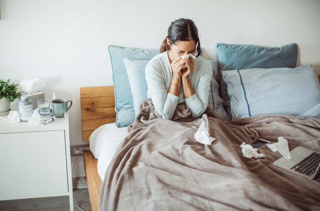woman sick in bed with a cold