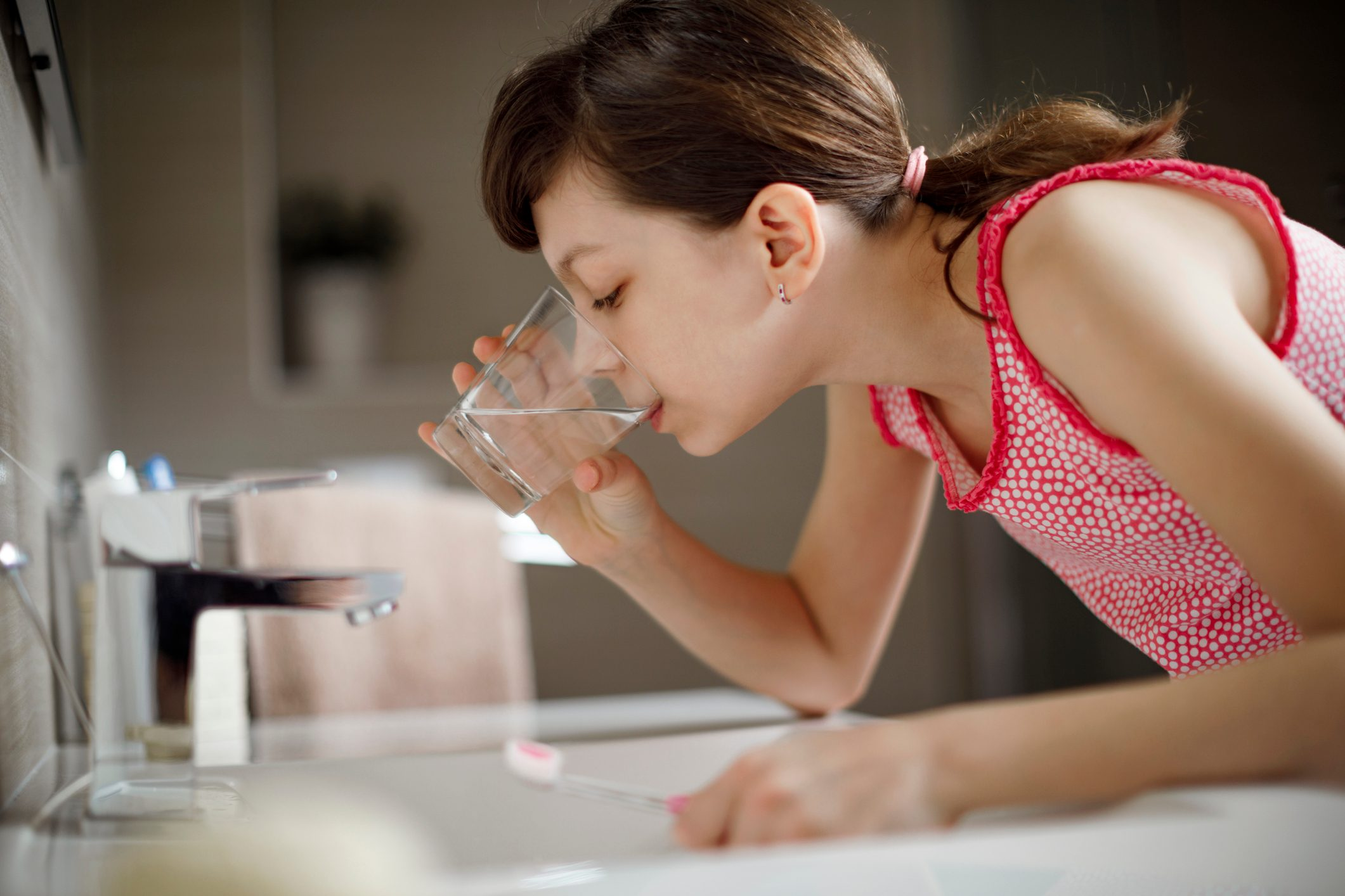 young girl rinsing mouth with water