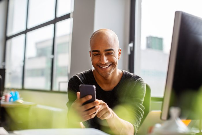 man at work looking at smartphone and smiling