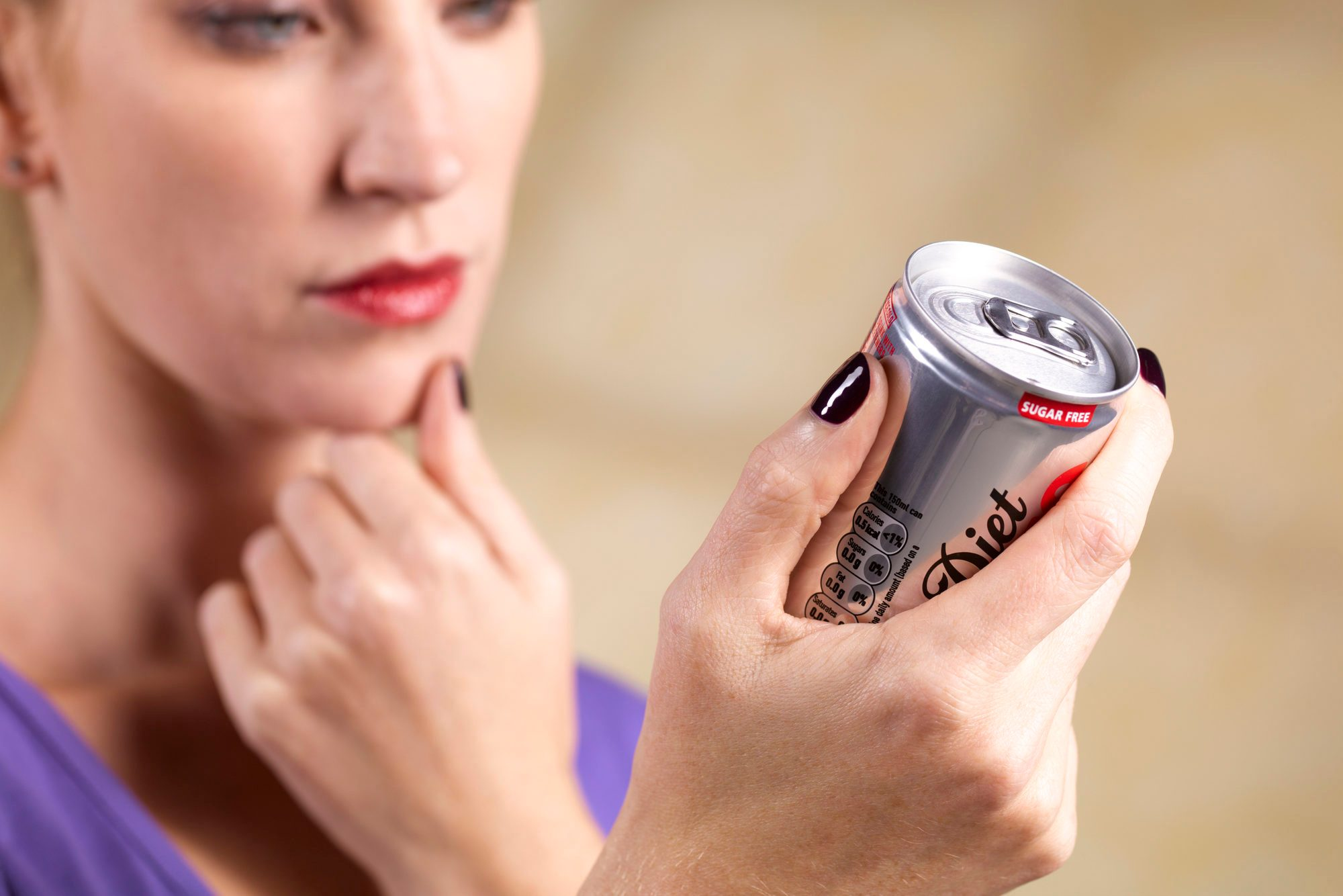 woman looking at diet coke can