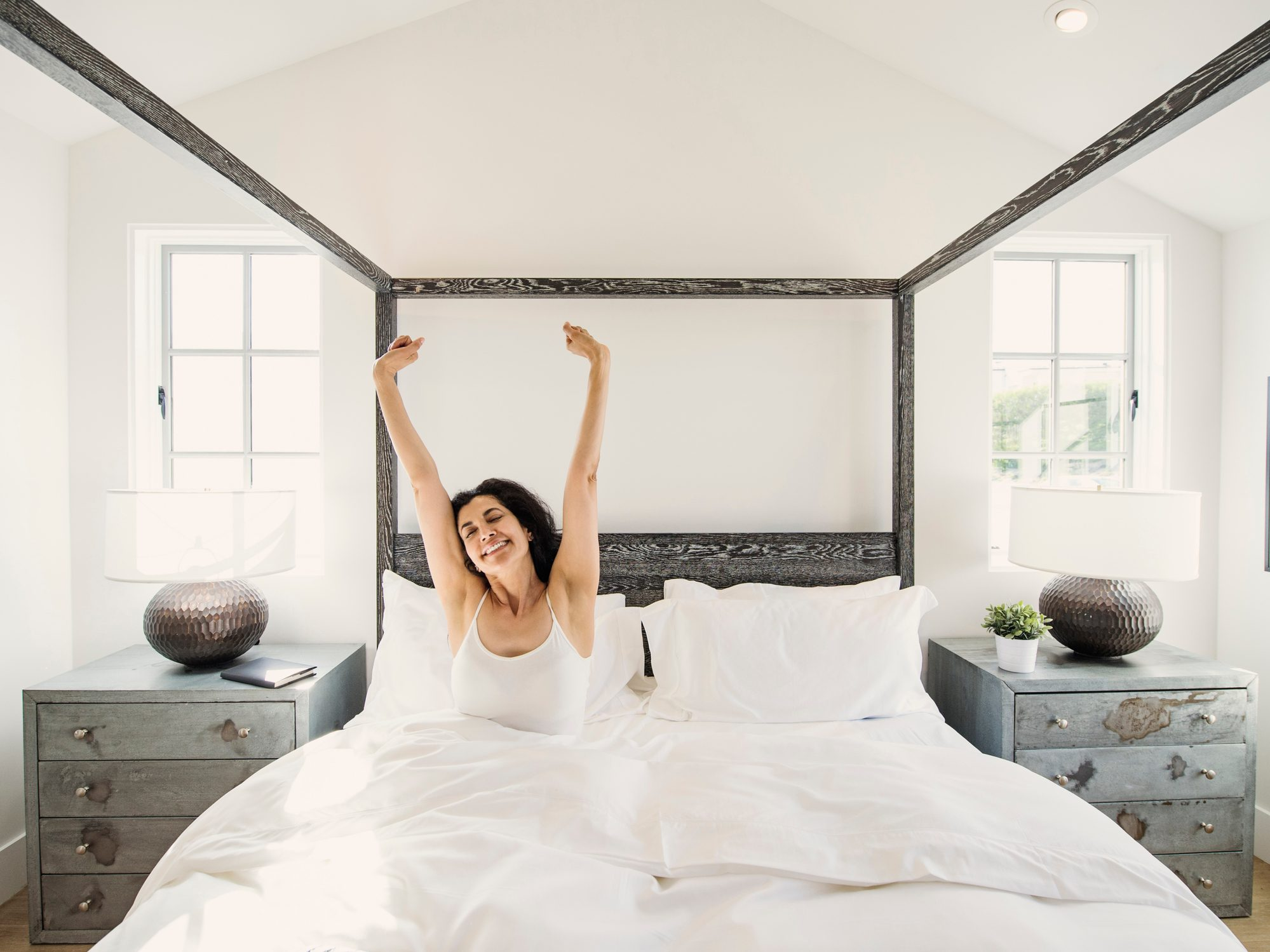 woman waking up happy in bed in the morning