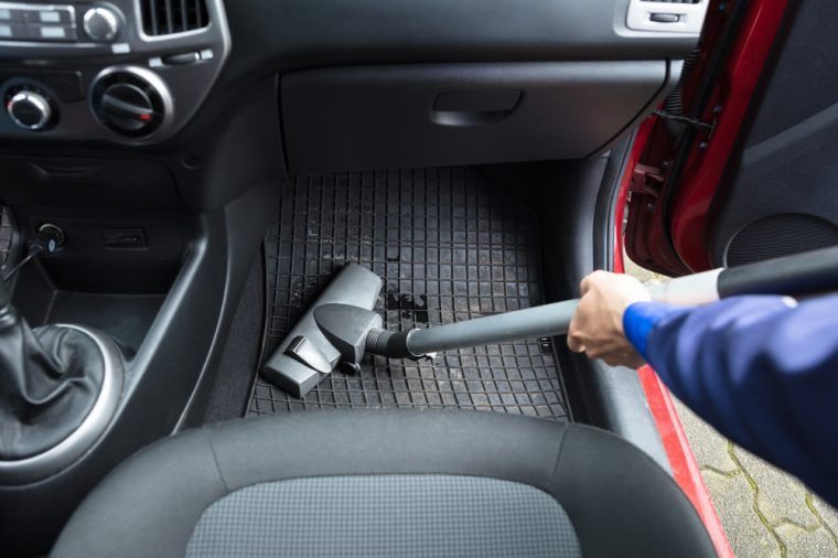 A person vacuuming a car mat with a vacuum cleaner.