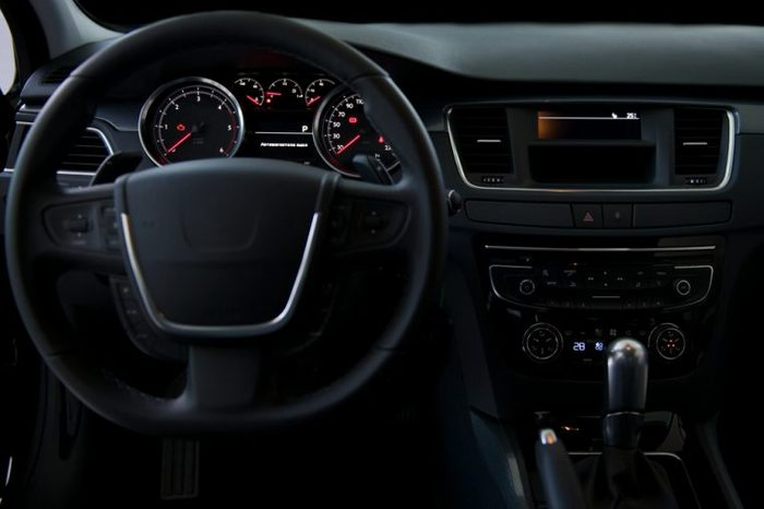 A black dashboard and steering wheel of a car interior.