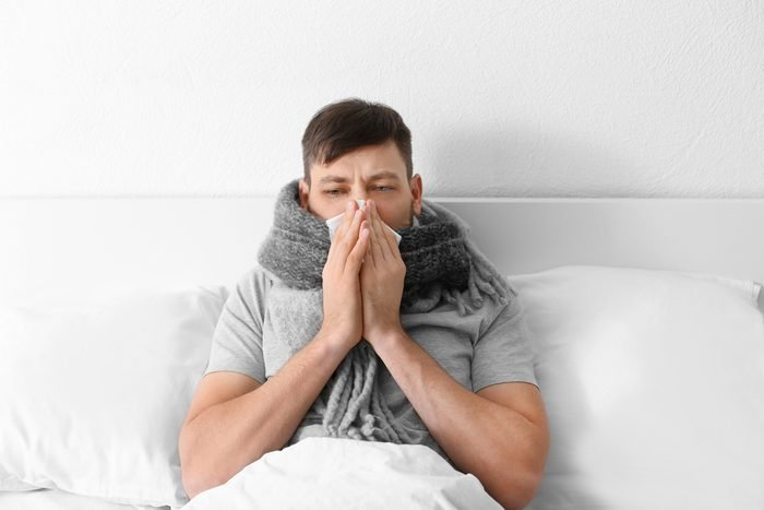 Young ill man in bed at home