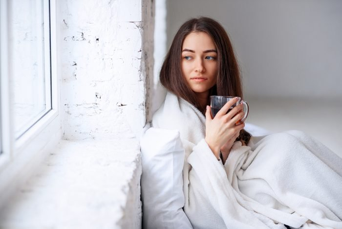 Close up of beautiful young woman in warm plaid with hot cup of tea in hands. Sickness and illness. Sick unhealthy female drinking warm drink indoors.