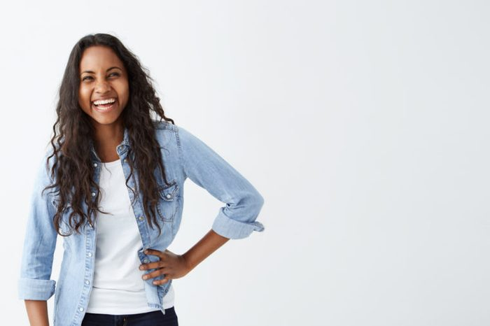 People, leisure and lifestyle concept. Good-looking young Afro-American woman with long wavy hair wearing stylish clothing smiling broadly, laughing happily at someone`s joke, having fun indoors.