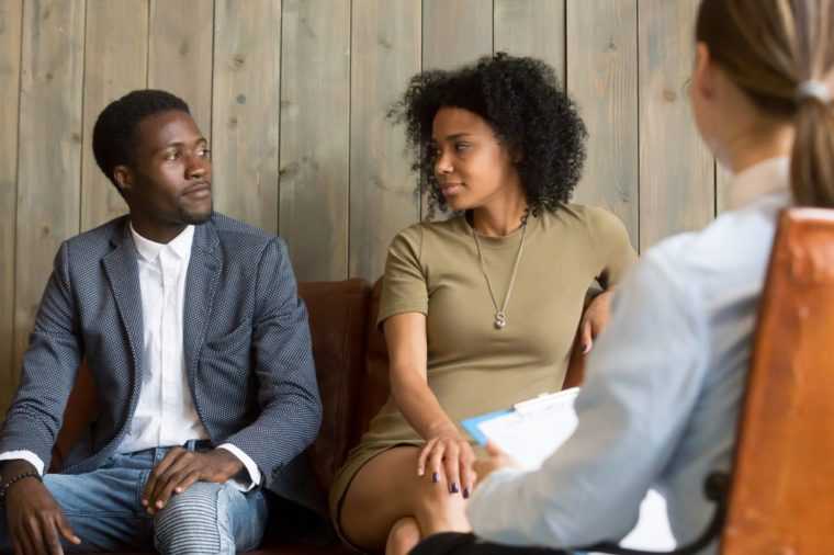 Reconciled black husband and wife looking at each other after successful psychological treatment from relationship counselor, African spouses make peace at therapy session, lovers ready to compromise