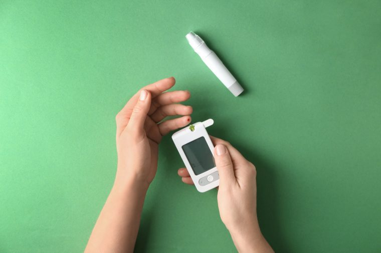 Woman measuring glucose level with digital glucometer on color background. Diabetes control