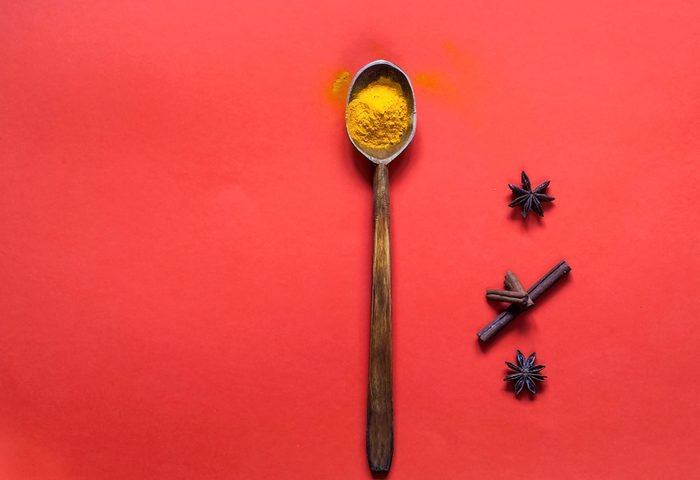 Wooden spoon with turmeric and spices on the background of living coral. The trend colour of the year 2019. Copy space, closeup