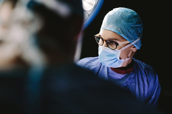 Surgeon wearing medical mask with medical team performing surgery in hospital operation theater.