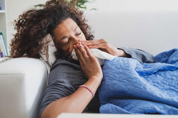 Sick black woman at home blowing her nose