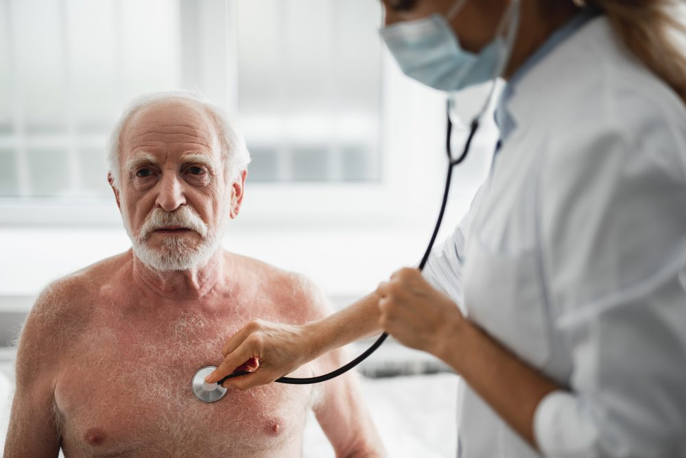 Shirtless elderly man being examined by a female doctor with a stethoscope
