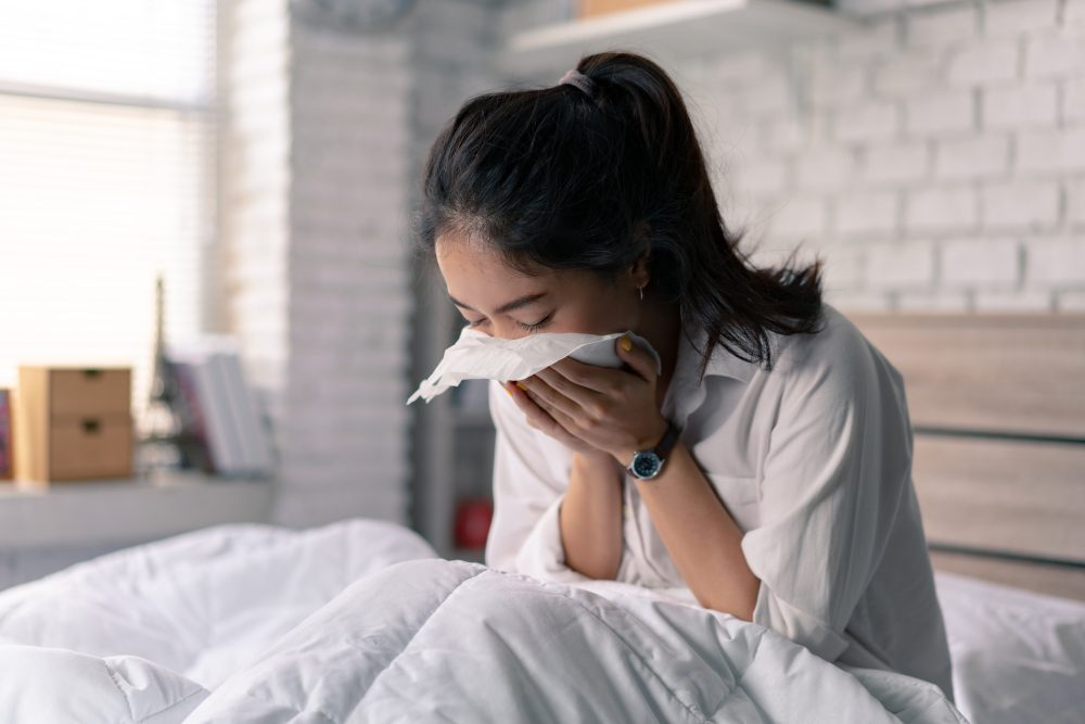 Asian woman in bed, sneezing into a tissue