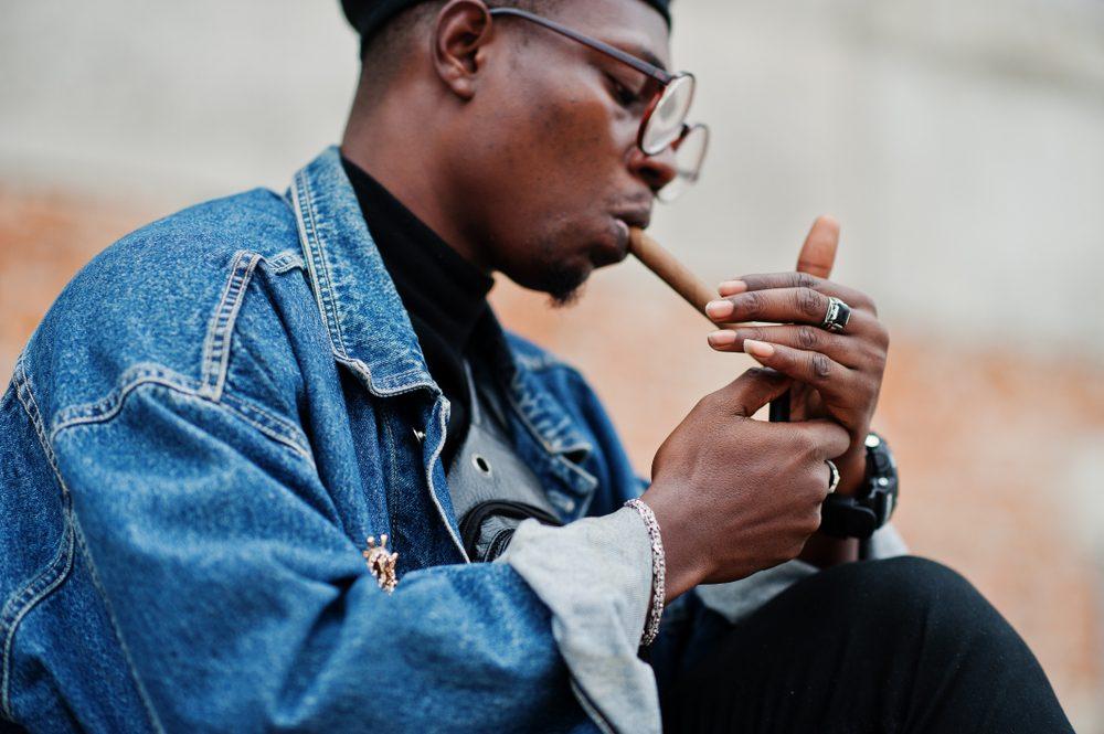 Black man in a denim jacket, beret, and eyeglasses lights a cigar.