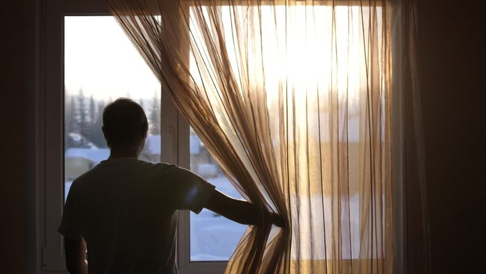 Young male opens curtains to bright sunny winter day and looks out of window through the sun during sunrise