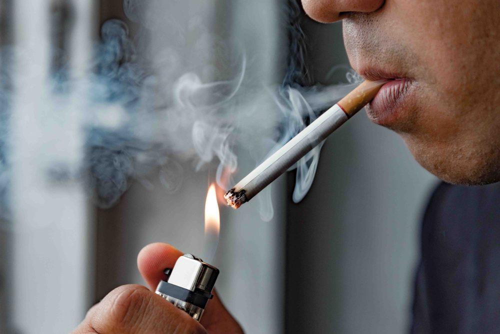 Close up young man smoking a cigarette.