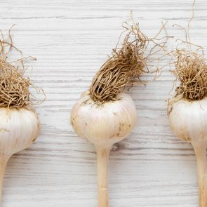 Garlic bulbs on white wooden table, overhead view. Copy space.