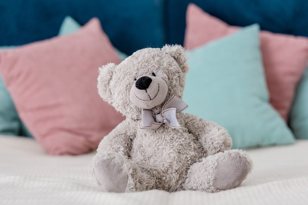 teddy bear sitting on a bed with pillows