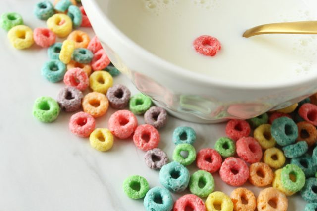 Close up view of cereal bowl with one piece of cereal and dry cereal spilled around it. Empty calories concept. Copy space.