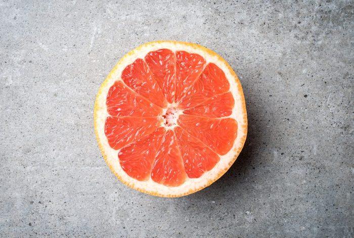 Red grapefruit on stone background